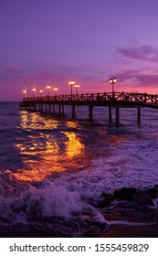 Long pier on the sea in Marbella, Costa del Sol, Spain. Illuminated wooden jetty on a beach in Marbella during sunset. Pier of marbella. Coastal pier into the Mediterranean sea in Marbella, Spain.