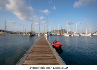 Long pier with red boat in the marina, Mindelo bay, Cape Verde.