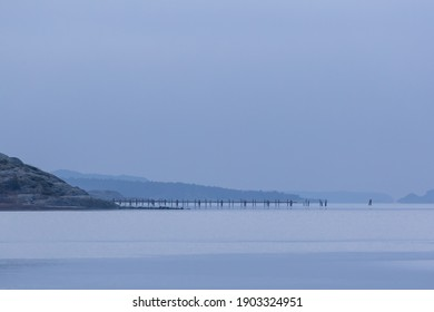 Long pier stretching out into the sea on hazy day in Sweden