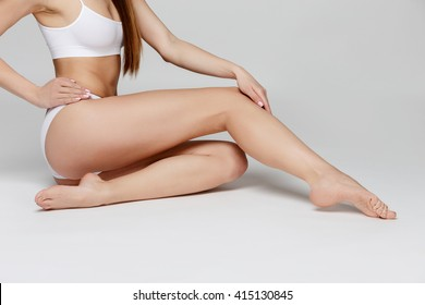 Long pretty woman legs, isolated on grey background