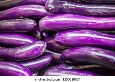 Long purple chinese eggplants fruits, also known as aubergine or brinjal fruits. Bunches of fresh long chinese eggplant at the farmers market