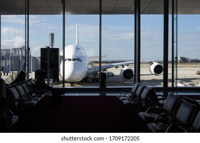 Long range airliner plane waiting in front of an airport seen from the interior of the terminal, from a waiting room where people usually wait to check in and to board the aircraft.