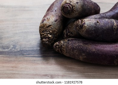 a lot of long red beetroots on a rustic wooden background, top view