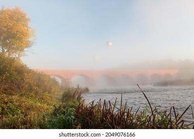 Long red brick bridge and flying hot air balloons in foggy, sunny morning, Kuldiga, Latvia.