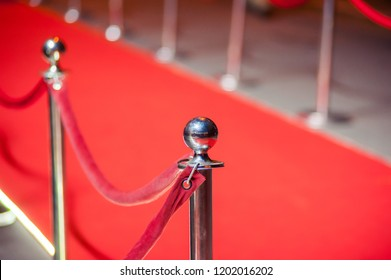 Long red carpet between rope barriers on entrance.