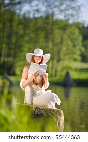 Long red hair romantic woman relax by lake with book on sunny day