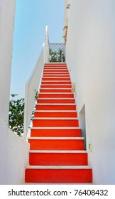 Long red staircase and traditional architecture on island of Santorini in Fira, Greece.