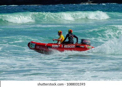 LONG REEF, NSW, AUSTRALIA - DECEMBER 26, 2006: Two surf lifesavers in an inflatable rescue boat patrolling the beach at Long Reef, Australia.