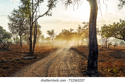 Long road in to the distance at sunset with light beams and smoke in Zambia Africa