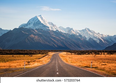 A long road leading to a large snow capped mountain on a sunny day