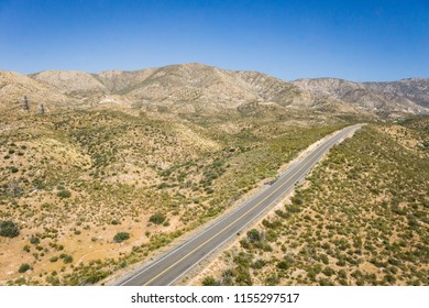 Long road leads through the dry desert hills in southern California's Mojave desert.