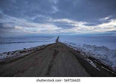 Long road through the snowy winter prairie