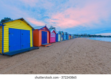 Long row of colorful bathing houses at pink sunrise in Melbourne, Australia