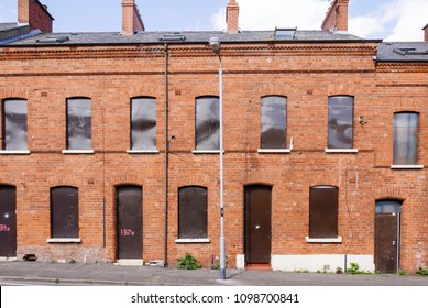 A long row of derelict houses in a street boarded up with steel plates.