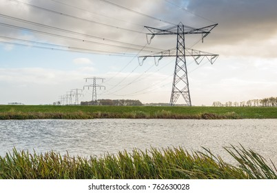 Long row of electricity pylons in a rural area with a small river on a cloudy day. It is autumn in the Netherlands.