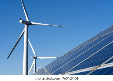 Long row of industrial solar panels with a large wind turbine in the background