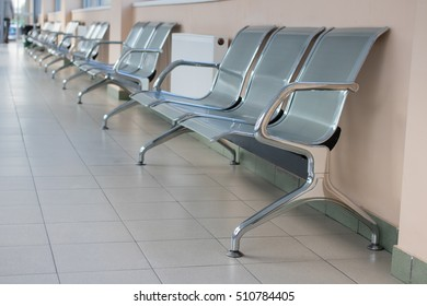 A long row of metal chairs in the hallway of the building