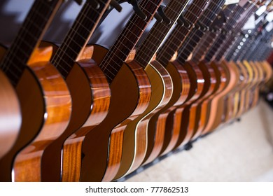 long row of new acoustic guitars in store