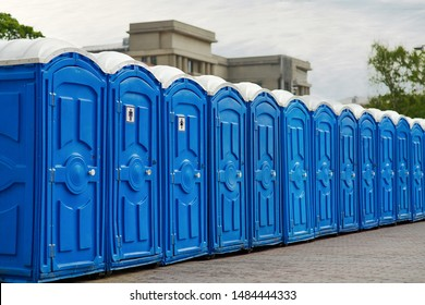 Long row of portable bio toilet cabins in a city street. Line of chemical toilets for the holiday, festival and crowd of people. Blue cabines of bio toilets in the city center. WC.