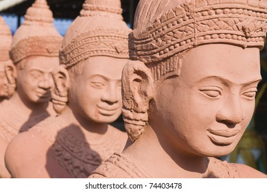 Long row of traditional statues guarding the entrance to a Buddhist temple