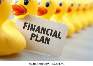 A long row of yellow rubber ducks with a sign that says Financial Plan on it.