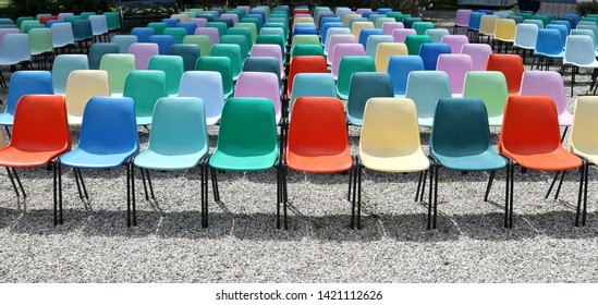 Long rows of empty colorful  plastic chairs geometrically arranged under the sun. Texture and background. Copy space.
