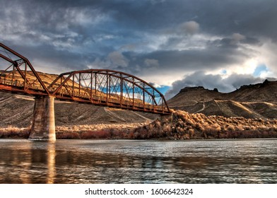 Long rusted bridge under a cloudy sky in a high desert scene looking up from the water's edge
