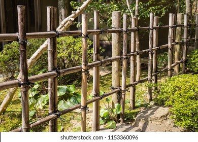 A long, rustic bamboo fence at the edge of a lush green Japanese garden park in the summer in Japan.