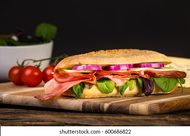 Long sandwich with sausage, chees and lettuce on wooden tale.
