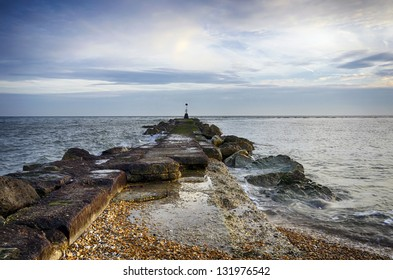 A long sea groyne with beacon on the beach at Hengistbury Head near Bournemouth in Dorset.