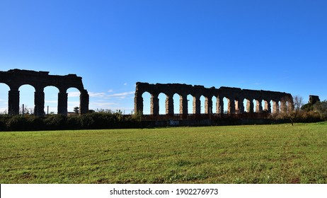 A long series of arches of a backlit aqueduct bordered by a green lawn and the blue sky