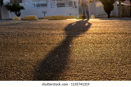 Long shadow of a man standing on the street