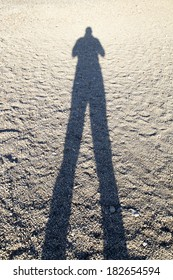 Long shadow of the man standing on the sandy beach