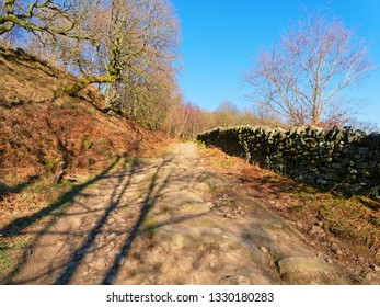 Long shadows point the way up a footpath between a steep bank and a dry stone wall in the Derbyshire Peak District.