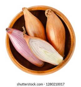Long shallots, whole and sliced, in wooden bowl.