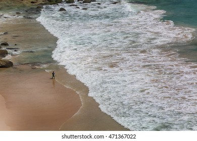 Long shoreline from above, lonely surfer walking along the beach line