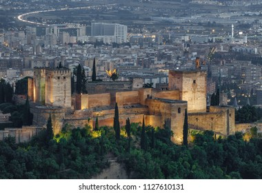 Long shot of the ancient arabic fortress of Alhambra with Granada city in the background at night