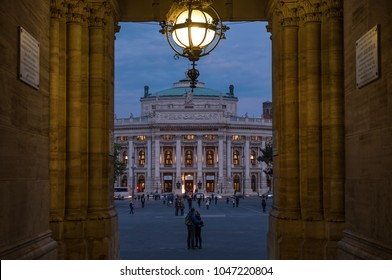 Long shot of Burgtheater in Vienna framed through the arch of Rathaus as the theatre lights come on