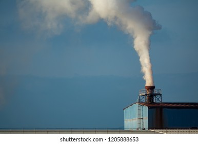 Long shot of factory smokestack with smoke