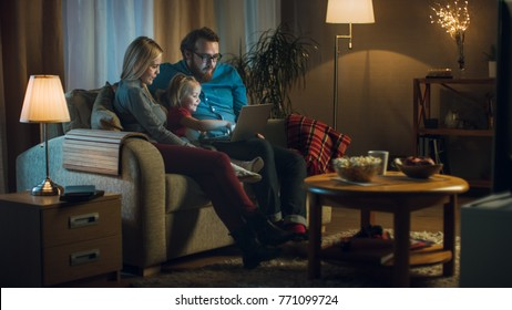 Long Shot of a Father, Mother and Little Girl Watching TV. They Sit on a Sofa in Their Cozy Living Room, Father Holds Laptop on His Knees. It's Evening.