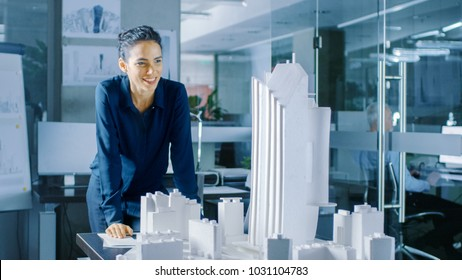 Long Shot of the Female Architectural Designer Adding Component to a Building Model, She Works on a City District Urban Planning Project. Beautiful Woman in Stylish Office. Long Shot.