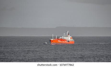 Long shot of large boat near gray ocean coast