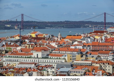 Long shot of lisbon roofs, tagus river and 25th april bridge over them all