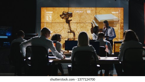 Long shot of Mars mission leader giving briefing in control room