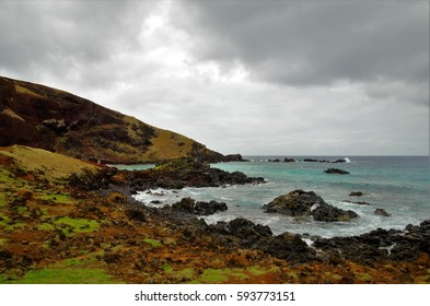 Long shot of the Ovahe beach, a small cove surrounded by red cliffs in Easter Island, Rapa Nui, Chile, South America