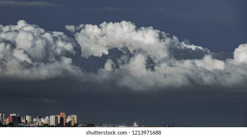 Long shot of skyscrappers near sea with stormy clouds over them