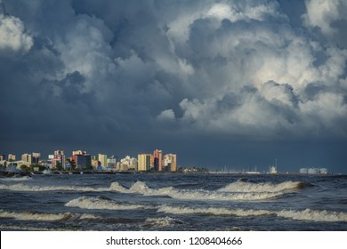 Long shot of stormy clouds over coastal city buildings