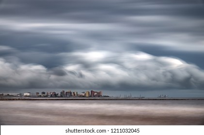 Long shot ultra long exposure of skyscrappers near sea with stormy clouds