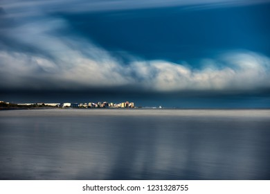 Long shot ultra long exposure of skyscrappers and silk sea with stormy clouds over them