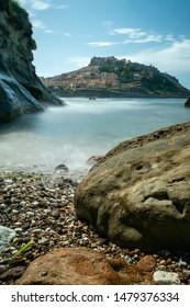 long shutter picture of castelsardo. rocks and foggy water